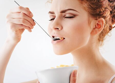 Young pretty girl eating corn flakes Stock Photo