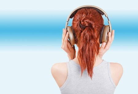 Girl with red hair in big headphones Stock Photo