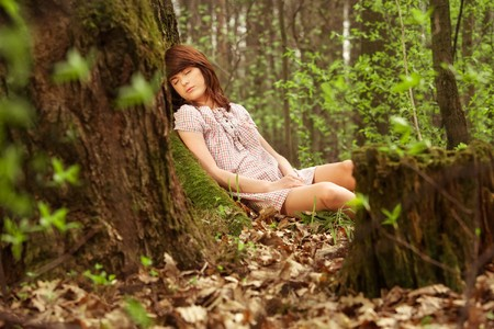 Young pretty girl sleeping in the forest photo