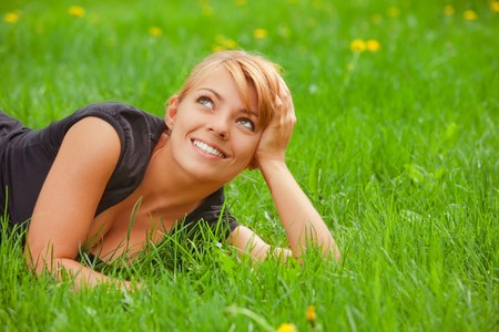 Young pretty girl lying on green grass photo