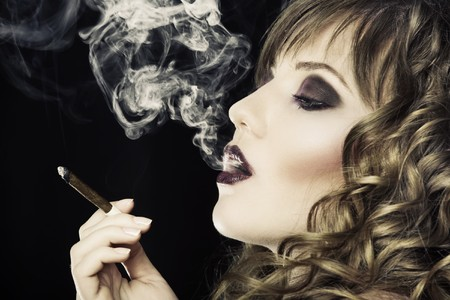 Young pretty girl is smoking cigarette photo