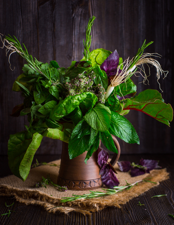 darkwood: Bouquet of fragrant herbs in a clay jug on darkbackground, in Rustic style Stock Photo