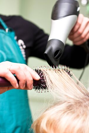 Hairdresser dries the hair in a beauty salon photo