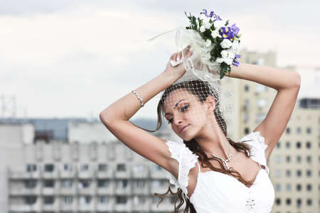 portrait bride in wedding dress on background of city photo