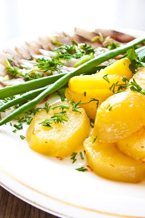 Potatoes with herring and greens on plate photo