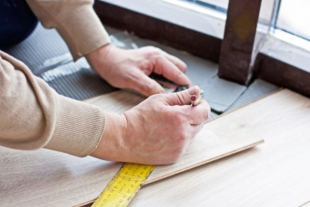 worker makes markup before laying laminate flooring photo