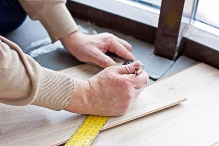 Worker Makes Markup Before Laying Laminate Flooring Stock Photo