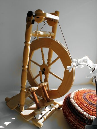 Old craft in new dress. Spinning wheel beside crochet pillow.