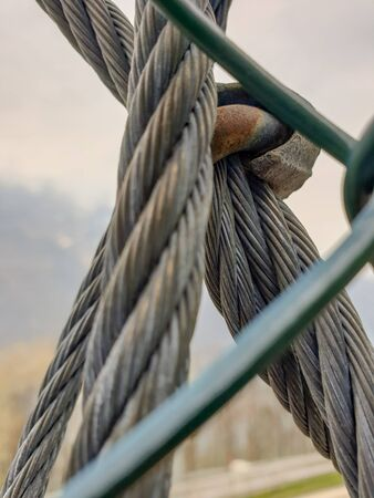hick knot made of a metal rope with several strands in grey, green and blue next to a delicate metal grid. a blurred landscape with trees in the background.