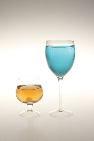 glass and wine globet with transparent blue and champagne liquid