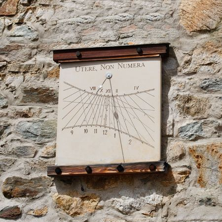 Sundial on a stone wall at a mountain hut in the Austrian Alps. The inscription means Use the hours, dont count them. photo