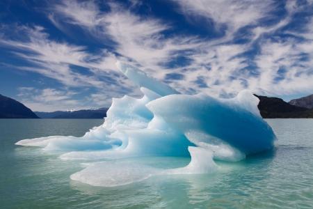 Iceberg bleu flottant dans un fjord en Patagonie, au Chili. Formations nuageuses dramatique et ciel bleu.
