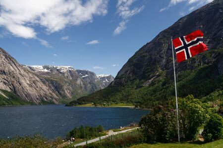 fiord: Norwegian flag in the foreground. Majestic Hardangerfjord as seen from the village of Eidfjord in the background.