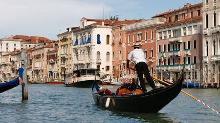 A Venetian gondolier propels a gondola on the Grand Canal in Venice, Italy. Traditional Venetian houses in the background.
