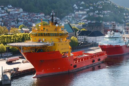 moored: Oil Rig Supply Boat at Bergen Harbor, Norway. City of Bergen in the background.