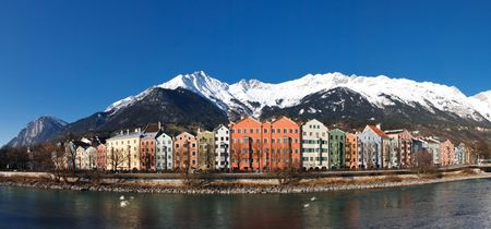 Panoramic View of Colorful Houses at the Inn Riverside in Innsbruck, Austria. Clear blue sky. Snowy Mountains.