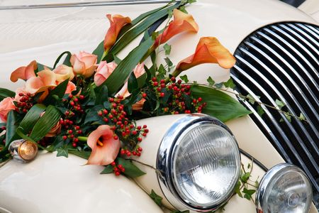 Close-up of Vintage Wedding Car Decorated with Flowers.