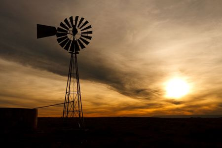 ニュー メキシコ州、アメリカ合衆国で夕暮れ時の回転ブレードとポンプ水のための古いファーム風車