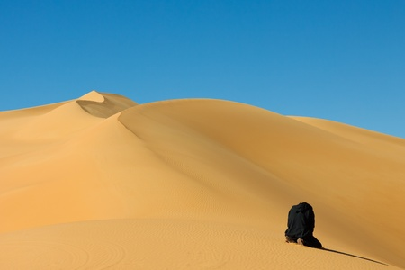 desierto del sahara: Hombre musulm�n rezando en el desierto del Sahara, Libia desierto - mar de arena de Awbari,