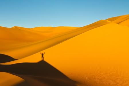 Shadow of a man on top of a huge sand dune at sunset in the Awbari Sand Sea, Sahara Desert, Libya photo