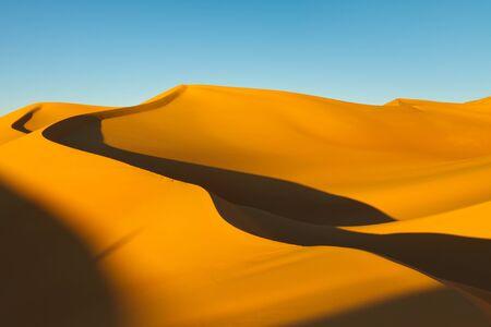 desierto del sahara: Enormes dunas de arena al atardecer en el mar de arena de Awbari, desierto del Sahara, en Libia. Foto de archivo