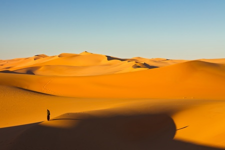 sahara desert: Lone man in the sand dunes at sunrise - Murzuq Desert, Sahara, Libya