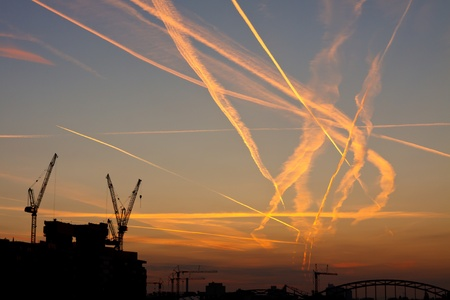 congested: Contrails crossing each other. Congested airspace over Frankfurt, Germany, at sunrise. Stock Photo