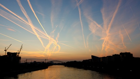 congested: Contrails crossing each other. Congested airspace  over Main River in Frankfurt, Germany, at sunrise. Stock Photo