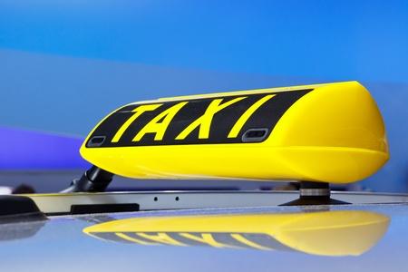 照らされたタクシーはドイツにサインインします。青色の背景色。 写真素材
