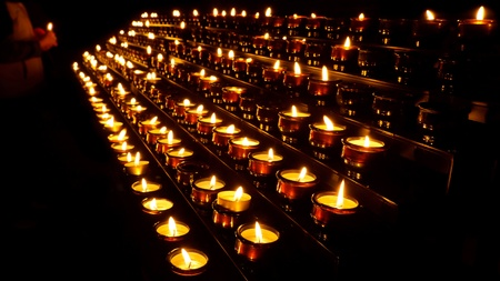 prayer candles: A person is lighting a prayer candle in a church.