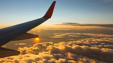 airplane wing: View from an airplane flying high above the clouds into the sunset. Stock Photo