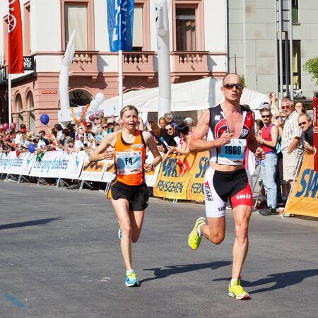 gutenberg: MAINZ, GERMANY - MAY 8: Olga Kotovska (left) of the Ukraine passes through Gutenbergplatz and later finishes second fastest at the Gutenberg Marathon on May 8, 2011 in Mainz, Germany. Editorial