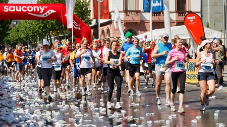 gutenberg: MAINZ, GERMANY - MAY 8: Runners hydrate at the water station on Gutenbergplatz near the 13 km mark at the Gutenberg Marathon on May 8, 2011 in Mainz, Germany. 9,500 runners participate in the event. Editorial