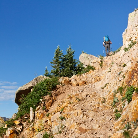 san juans: Hiker climbing up a steep trail in the Rocky Mountains in Colorado. Stock Photo