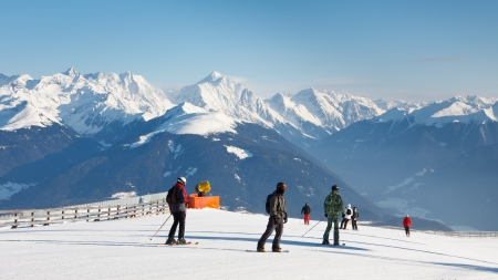 Skiers enjoy the fantastic alpine panorama on a sunny winter day. photo
