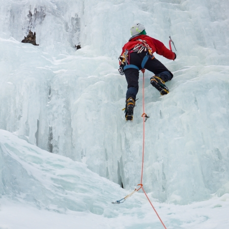 tal: An ice climber makes his way up on a frozen waterfall near Prags, South Tyrol, Italy  Stock Photo