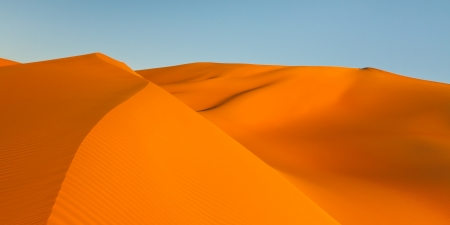Panoramic view of golden sand dunes at sunset. photo