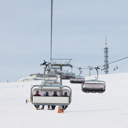 Skiers in chairlift approach the summit station at a ski resort in South Tyrol. photo