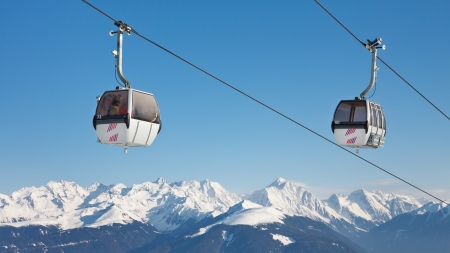 Gondolas of a ski lift above snow covered mountain peaks on a sunny winter day.