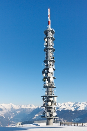 Radio tower on a snowy mountain summit on a crisp winter day. photo