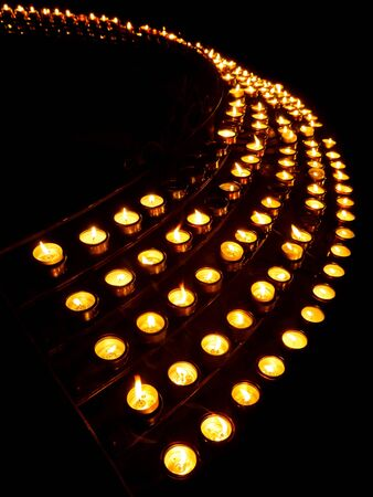 Rows of prayer candles light up the darkness in a church. photo
