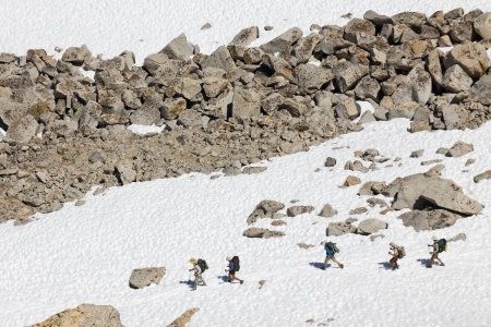 sierras: Hiking in the Sierra Nevada Mountains. Five hikers on a snowfield in Kings Canyon National Park, California, USA.