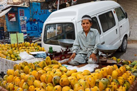 pakistani pakistan: RAWALPINDI, PAKISTAN - JULY 16: Unidentified Pakistani boy sells fruits at Raja Bazaar on July 16, 2011 in Rawalpindi, Pakistan. Raja Bazaar is the main shopping area in Rawalpindi.