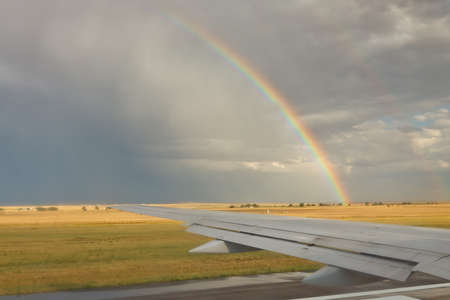 Airplane on runway at takeoff. Rainbow in the background. photo