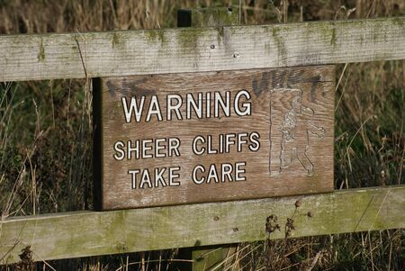 steep cliff sign: Warning  Sheer Cliffs Take Care Stock Photo