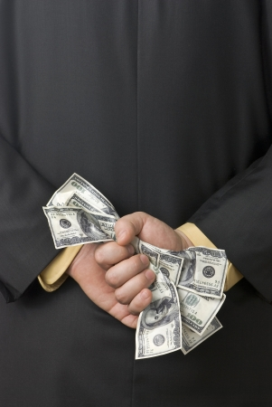 Dirty money grasped by a business man behind his back Stock Photo