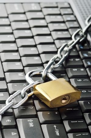 Locked chain on computer keyboard Stock Photo