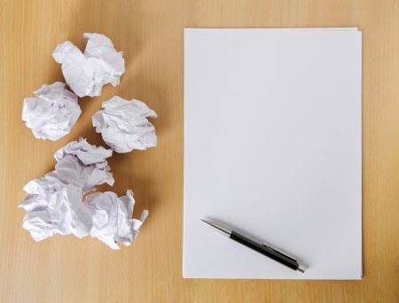 writers block: Crumpled paper balls and blank sheet of paper with pen