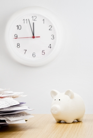 owe: Tax time. A stack of bills next to a piggy bank with a clock behind