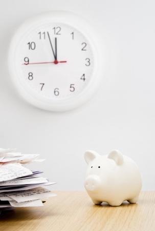 Tempo di imposta. Una pila di bollette accanto a un salvadanaio con un orologio dietro Archivio Fotografico